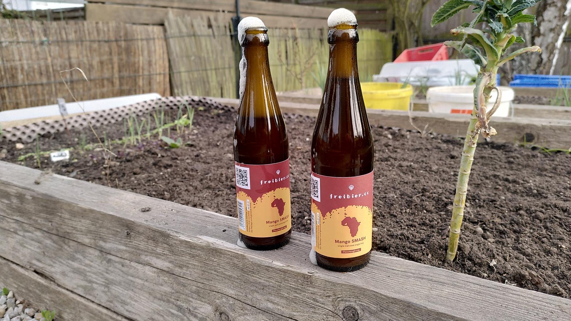 Zwei Mango SMASH Flaschen auf Hochbeet im Garten
